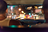 'Inside a Cuban locals only'' taxi colectivo at night. Because of the two monetary system in Cuba, and although forbidden by the Cuban government, colectivo drivers pick up tourists for payment in CUCs.. Drivers usually pick up 3-5 people per trip. The dr