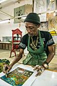 'A male Cuban artist painting a Cuban street scene, cigar in hand, in El Taller Experimental de Gr?ífica (Experimental Graphic Studio''), a cooperative graphic print shop and art studio in Old Havana or Habana Vieja, La Habana, Cuba.'''