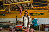 A young butcher with long dreadlocks stands behind his meat and a scale in a produce market known as Agropecuario 19 y B - in the Vedado section of Havana Cuba.