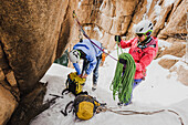 Two people preparing with ropes and anchor for ice climbing