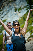 Young woman raising her hands while hiking on the Five Lakes Trail