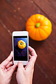 Close-up Of Person Hands Holding Smartphone Taking Picture Of Pumpkin On Wooden Table