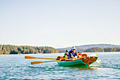 A Man With His Son And Their Dog In A Rowing Boat In Deer Harbor, Orcas Island, Washington, Usa