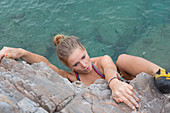 Elevated view of teen girl climbing above sea