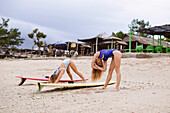 Two Young Women Doing Exercise Before Surfing At Beach