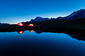 Camping tents reflected in the alpine lake at night Mont De La Saxe Courmayeur Aosta Valley Italy Europe