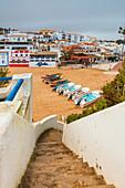 Boats on sandy beach frame the typical fishing village of Carvoeiro Lagoa Municipality Algarve Portugal Europe