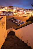 Boats on sandy beach frame the typical fishing village of Carvoeiro at dusk Lagoa Municipality Algarve Portugal Europe
