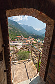 A stone arch of an old alley frames the typical village of Porto immersed in the green vegetation Southern Corsica France Europe