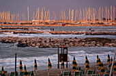 The sunset on the Rimini beach lights the rough seas and the small touristic harbor with moored sailing boats on the docks of stones, Emilia Romagna, Italy