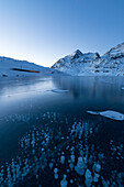 Ice bubbles frame the snowy peaks reflected in Lago Bianco Bernina Pass canton of  Graubünden Engadine Switzerland Europe