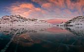 Panorama of the frozen Lago Bianco under pink clouds at dawn Bernina Pass canton of  Graubünden Engadine Switzerland Europe