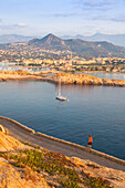Tourist on a road admires the sail boat in the clear sea around the village of Ile Rousse Balagne Region Corsica France Europe