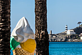 A big wafer cone as an advertisement in the harbour with view at the lighthouse, Port de Sóller, Mallorca, Spain