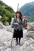 old lady carrying firewood on her back, Theth, Albanian alps, Albania