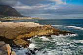Seelandschaft über stürmisches Meer und Felsen bei der Einstellung der Sonne bei Sievers Point, Hermanus, Südafrika, Afrika