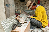 'Worker carving stones with the mantra ''om ma ni pa me hum'', Shangrila's Monastery, a beautiful and famous place with more than 20 buddhist temples; Shangrila, Yunnan province, China.'
