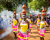 'Women wearing brightly coloured traditional clothing walk and carry pottery on their heads; Uganda'