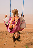 'A Young Bedu Girl Plays On Her Desert Swing; Wahiba Sands, Oman'