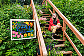Woman sitting on stairs in a lush garden, Seldovia, Southcentral Alaska, USA