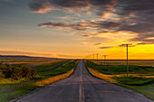 'Golden sunset over farmland and a rural road; Herschel, Saskatchewan, Canada'