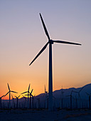 'Silhouette of wind turbines in a field with a mountain range in the distance at sunset; Palm Springs, California, United States of America'