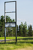 'A old retail sign along the road with a message showing that they have left the premises; Alberta, Canada'