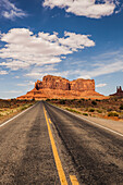 'A road leading to a rugged rock formation in the desert; Arizona, United States of America'