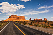 'A road leading to rugged rock formations in the desert; Arizona, United States of America'