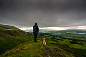 'A man stands with his dog on a grassy hill looking out over the lush, green landscape under a stormy sky; North Yorkshire, England'