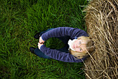 'High Angle View Portrait Of A Teenage Girl Sitting Against A Hay Bale; Homer, Alaska, United States Of America'