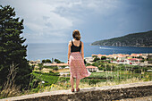 Young Woman Looking Out Over Town of Komiza, Island of Vis, Croatia