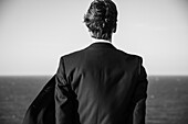 Rear View Portrait of Young Adult Man in Suit Looking out to Sea