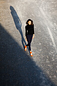 Portrait of Confident Young Adult Woman in Black Clothes and  Orange Shoes Walking, High Angle View