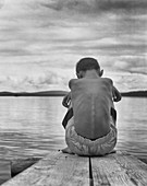 Rear View Portrait of Sad Boy Sitting Hugging His Knees at End of Dock on Lake