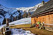 Frau auf Skitour macht an Almhütte Pause, Plankowitzspitze, Radstädter Tauern, Kärnten, Österreich