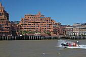 Touristenboot passiert einen Appartmentblock an der Themse, Wapping, London, England