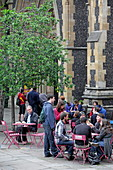 Visitors of Borough Market enjoy their purchases, Southwark Cathedral, London, England