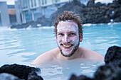 Young man wears silica mud mask and smiles while bathing at The Blue Lagoon, the famous wellness thermal pool with its typical blue-white water in winter time, near Grindavik, Reykjanes, Iceland, Europe