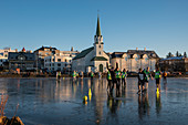 School children play soccer on frozen Tjörnin lake with Fríkirkjan (Frikirkjan) church behind, Reykjavik, Iceland, Europe