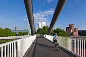 Cyclist on a bridge at Medienhafen, view to Neuer Zollhof (Architect: F.O. Gehry), Duesseldorf, North Rhine-Westphalia, Germany