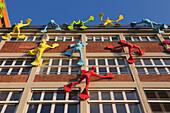 Flossi figures at the facade of the Roggendorf house, Medienhafen, Duesseldorf, North Rhine-Westphalia, Germany
