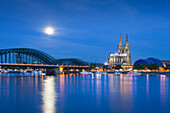 Full moon, view over the Rhine river to Hohenzollern bridge, Cologne cathedral and musical dome, Cologne, North Rhine-Westphalia, Germany