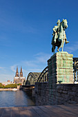 Equestrian sculpture at Hohenzollern bridge, view over the Rhine river to Museum Ludwig and Cologne cathedral, Cologne, North Rhine-Westphalia, Germany