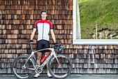 Young man standing at a wall next to his racing cycle at the Kitzbühler Alps, Kitzbühlerhorn, Tyrol, Austria