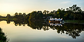 'Reflections in a tranquil river at sunset with a tour boat along the shoreline; Chiang Rai, Thailand'