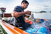 'A fisherman working with nets on his fishing boat; Ko Samui, Chang Wat Surat Thani, Thailand'