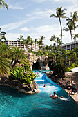 'Pool with a river and swimmers at the Grand Wailea; Wailea, Maui, Hawaii, United States of AmericaPool mit einem Fluss und Schwimmer an der Grand Wailea, Wailea, Maui, Hawaii, Vereinigte Staaten von Amerika'