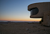 'A colourful sunset over the horizon with a viewing window along a curved building for a view; Mitzpe Ramon, South District, Israel'