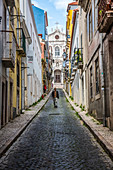 'Guy descending a narrow street with Igreja Paroquial das Merces in the background; Lisbon, Portugal'
